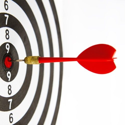 Close-up dart board with a red arrow that hit the center of the target