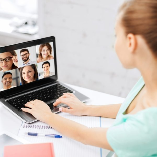 woman with laptop has video call with colleagues