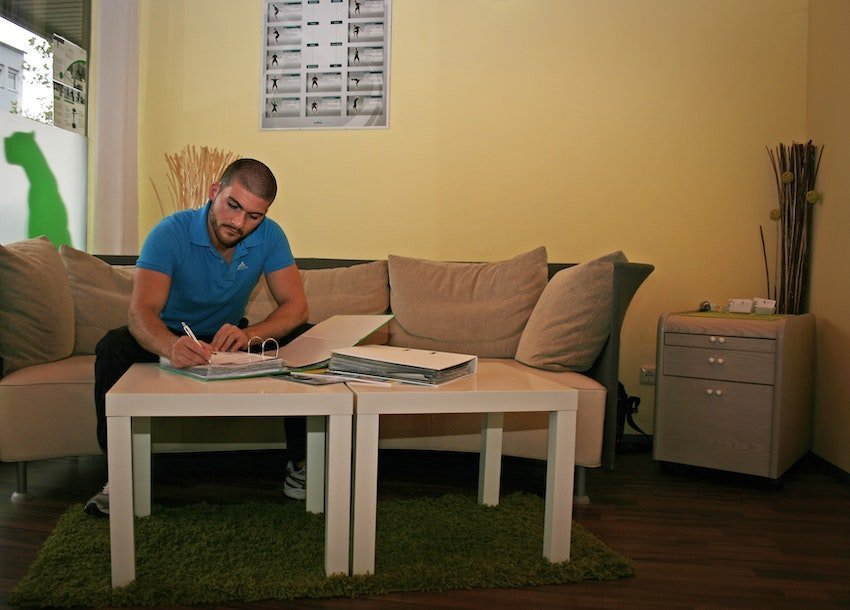 man sitting on the coach and writing, maintaining work home boundaries