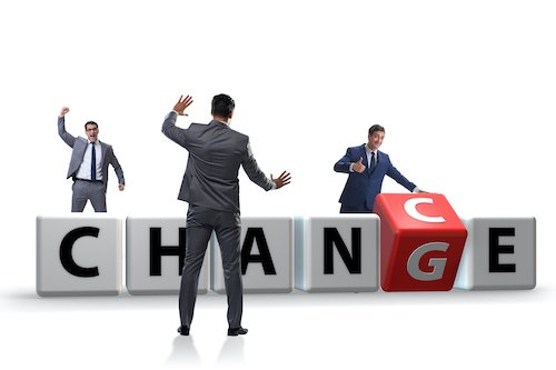 Businessmen dancing around building blocks that spell out the word 'change'