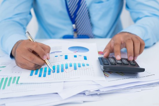 Financial manager analyzing charts and graphs to cut costs during covid-19