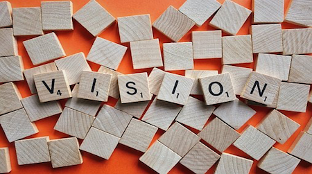 wood blocks spelling out the word 'vision'; a company vision is essential for success