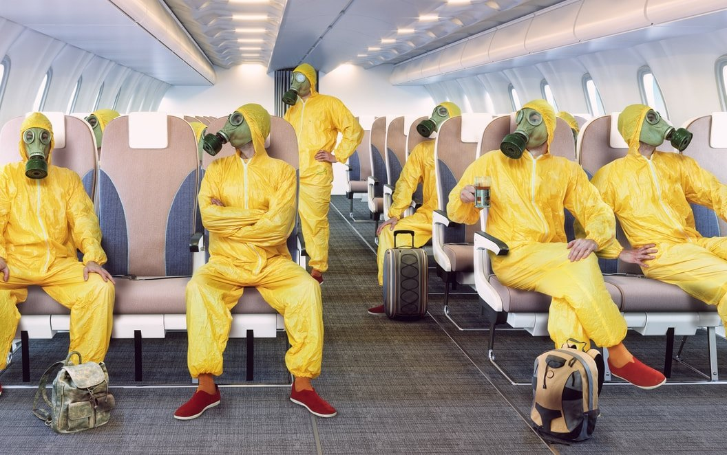 people wearing PPE in the airplane because of pandemic; the sharing economy will be different post covid-19