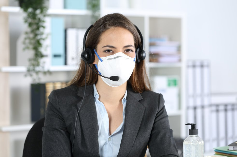 Call center employee wearing a mask as PPE as part of safe working procedures