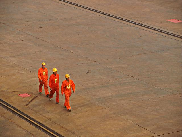 3 Industry workers in orange suits walking across ground