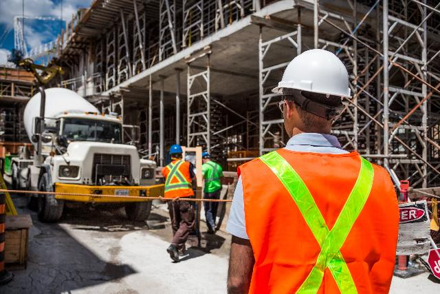 Construction site supervisor using frontline leadership skills with workers