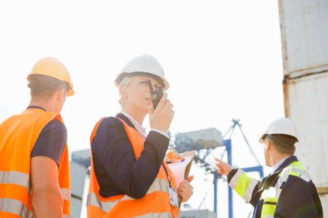 woman on construction site communicating safety effectively on walkie talkie