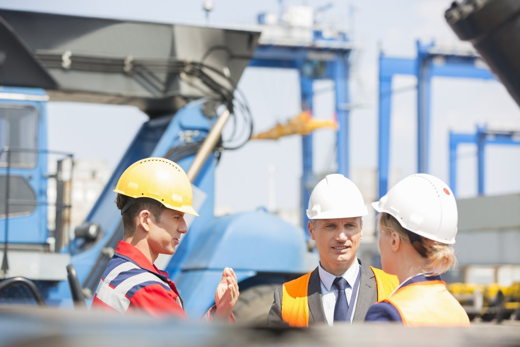 workers discussing and raising safety awareness in shipping yard