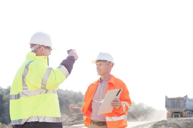 two employees in hardhats, sharing safety suggestions