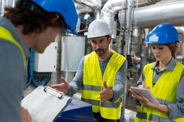 workers in yellow vests doing pre-job brief